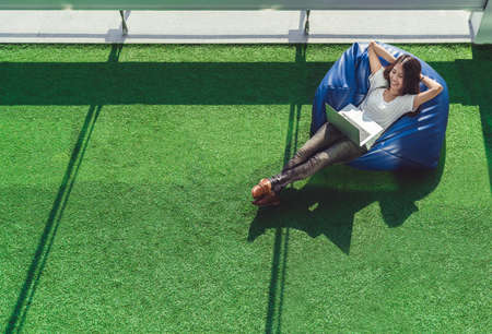 Asiatischer Student oder freiberuflich tätige Frau, die die Laptop-Computer, liegend auf Bohnentasche im Garten verwendet. Universitätscampus oder Parkszene. Bildung oder gelegentliches Geschäftskonzept. Kopieren Sie Platz auf grünem Grasyard
