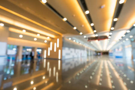 Blurred, defocused bokeh background of grand hallway, exhibition hall, or trade show event. International convention center, modern interior architecture, or commercial tradeshow organizer concept