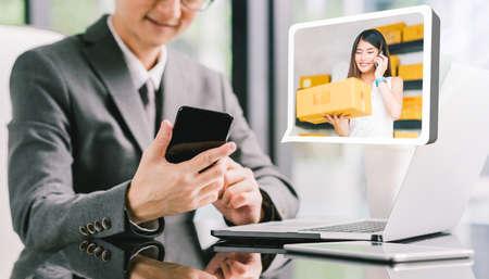 Geschäftsmann-CEO-Auftragsproduktkasten vom jungen weiblichen asiatischen Inhaber des kleinen Geschäfts, der Telefon, Laptop verwendet. Online-Marketing-Versand-Lieferservice, E-Commerce-Technologie oder Telemarketing Startup KMU