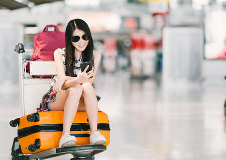 Young Asian girl using smartphone, waiting for flight at airport, sitting on baggage trolley or luggage cart. Mobile communication technology or travel abroad concept, with copy space Stok Fotoğraf