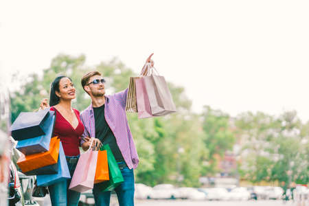 Multiethnic couple with shopping bags, man pointing at copy space on sky. Love, casual lifestyle, or shopaholic concept