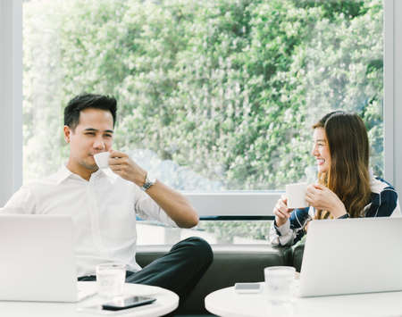 Young Asian couple or coworkers having coffee break while working on laptop computer at cafe or coffee shop. Leisure, casual work, love, or friendship concept. With copy space