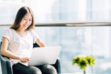 Beautiful Asian girl using laptop computer, smiling happily. College student or freelance worker in modern office. Education or technology or startup business concept with copy space
