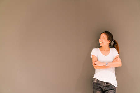 Beautiful Asian girl standing on grey wall background, looking at copy space Foto de archivo