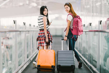 Two happy Asian girls traveling abroad together, carrying suitcase luggage in airport. Air travel or holiday vacation concept Stockfoto