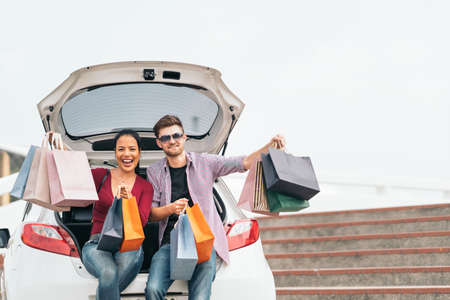 Multiethnic couple with shopping bags, smiling and sitting on white car. Love, casual lifestyle, or shopaholic concept. With copy space