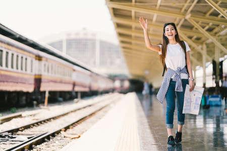 Aziatische rugzak reiziger vrouw bedrijf generieke lokale kaart en golvende hand op het station platform, zomervakantie reizen of jonge toeristische concept