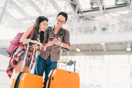 Asian couple travelers using smartphone checking flight or online check-in at airport, with passport and luggage. Air travel or mobile phone technology concept Imagens