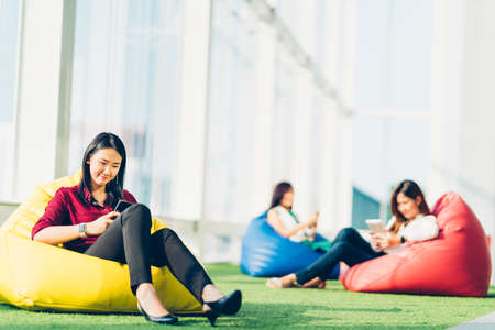 Group of Asian college student or business colleague using smartphone sit together in modern office or university campus. Social media network, internet dating app, or communication technology concept
