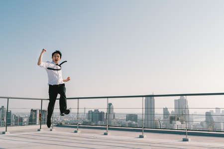 Young handsome Asian businessman jumping high, celebrate success winning pose on building rooftop. Work, job, or successful business concept. Cityscape background with copy space on sunny blue sky Stockfoto