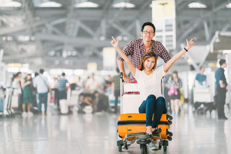Young Asian tourist couple happy and excited together for the trip, girlfriend sitting and cheering on baggage trolley or luggage cart. Holiday vacation travelling abroad concept, with copy space 스톡 콘텐츠