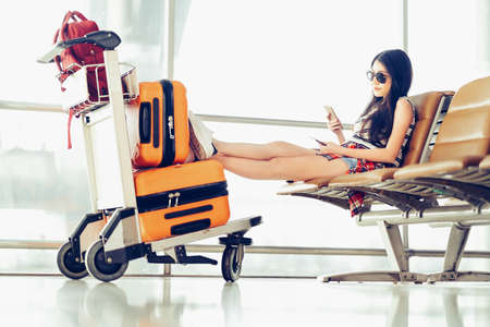 Young Asian traveler woman, university student sit using smartphone at airport, luggage and bag on trolley cart. Online check in mobile app, study abroad, or international tourism lifestyle concept