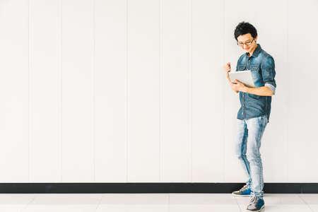 若いアジア人や大学の学生を応援デジタル タブレットを使用して成功すると、白い壁の背景にコピー スペースを祝います。教育、プロの仕事、情報