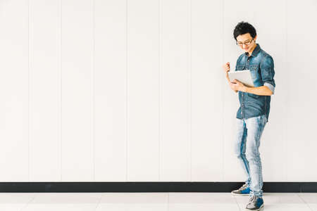 Young Asian man or college student using digital tablet cheering celebrate success, copy space on white wall background. Education, professional job, information technology or mobile lifestyle concept