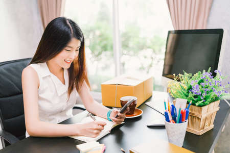 Young cute Asian small business owner work at home office, using mobile phone call, writing confirm purchase order on notebook. Income planning, casual CEO person, or creative telemarketing concept