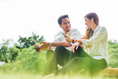 Young Asian lovely couple or college students sit listening to song music on smartphone together in park. Leisure activity, Online love, internet dating app technology, or casual lifestyle concept Stockfoto