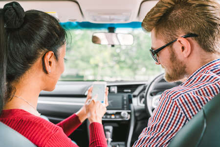 Multiethnic lover couple, white man and black Asian girl using navigator system app on smart phone in car. Modern gadget lifestyle, family travel activity, or online taxi call request service concept. Stock Photo