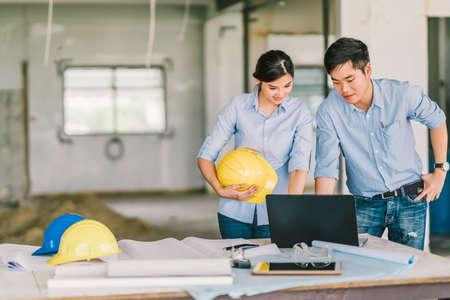 Jeune couple d'ingénieurs asiatiques travaillent ensemble à l'aide d'un ordinateur portable sur le chantier de construction. Réunion de brainstorming de génie civil, conception d'architecture ou concept de constructeur de maison. Avec l'espace de copie