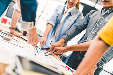 Group of multi-ethnic diverse team, business partner, or college students in project meeting at modern office or university. Five people pointing at diagram chart drawing. Creative or teamwork concept