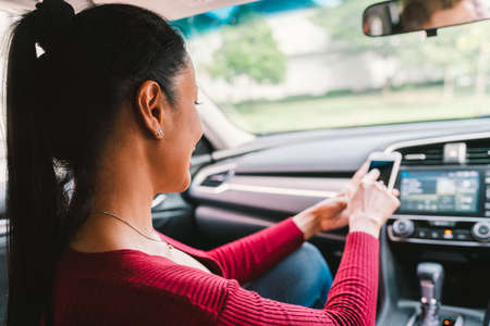 Woman using smartphone app on modern car. Mobile phone application, map navigation device technology, transportation, or crowdsourcing taxi concept Foto de archivo