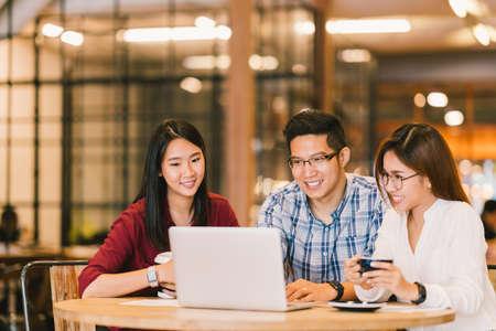 Grupo asiático novo ou estudantes universitários da faculdade universitária que usam o computador portátil junto no café ou na universidade. Negócios casuais, trabalho freelance, reunião de coffee break, e-learning ou conceito de atividade de e-commerce