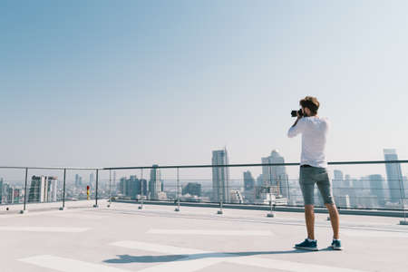 Young white Caucasian man taking cityscape photo on building rooftop on sunny day. Photography hobby, gadget technology, or leisure activity concept. With copy space on blue sky Stock Photo