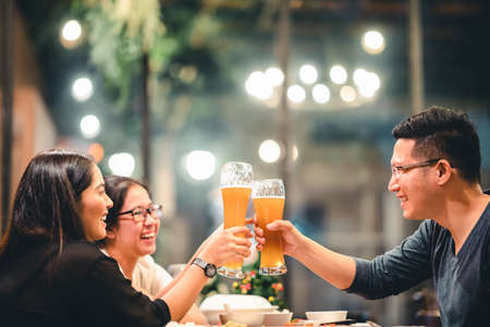 Group of Asian friends or coworkers cheering with beer, celebrating together at restaurant or night club. Young people toasting at party event after work. Success or friendship concept. Focus on glass