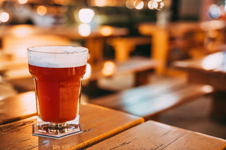 Fruit-flavoured beer or fruit juice on restaurant table with copy space on blur bokeh background. Happy event celebrations, nightlife at pub, dinner party, or alcoholic drinks advertisement concept