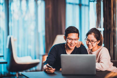 Young Asian married couple working together using laptop at home or modern office with copy space. Startup family business, SME entrepreneur, business partner, love relationship, or freelance concept 版權商用圖片