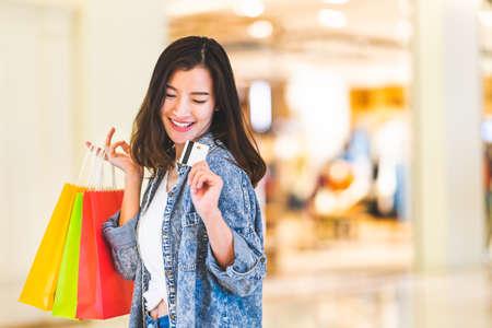 Sonrisa feliz hermosa mujer asiática en la tarjeta de crédito, sostenga bolsas de compras, copie el espacio en el fondo del centro comercial. Gente adicta a las compras, precio de oferta especial minorista, concepto de estilo de vida de actividad de vacaciones de vacaciones