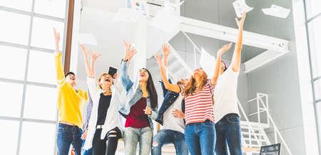 Das multiethnische, vielfältige, glückliche Team feiert den Projekterfolg und wirft Papier zusammen. Unternehmensgemeinschaft, Hochschulabschluss, Startup-Aktivität, Gehaltserhöhung oder erfolgreiches Konzept für kleine Unternehmen