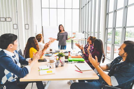 Multiethnic diverse group of creative team or business coworker clapping hands in project presentation meeting leading by Asian woman. Success teamwork, modern office work, or startup company concept Stock Photo