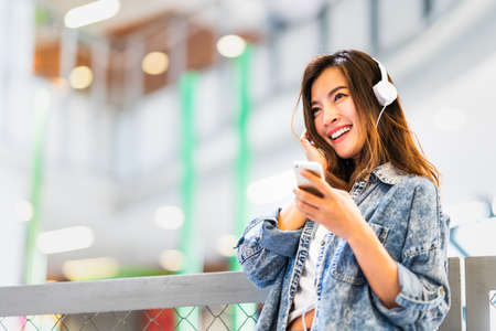 Beautiful young Asian girl listen to music using smartphone and headphone smile at copy space. Modern teenager lifestyle, college student hobby, youth culture or mobile phone gadget technology concept Foto de archivo - 106477521