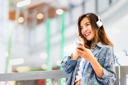 Hermosa joven asiática escucha música con smartphone y auriculares sonríe en el espacio de la copia. Estilo de vida adolescente moderno, pasatiempo de estudiante universitario, cultura juvenil o concepto de tecnología de gadget de teléfono móvil Foto de archivo