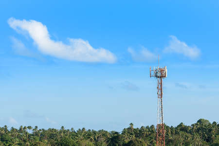 Cellular mobile antenna on telecommunication tower in tropic climate atmosphere, copy space on blue sky background. Mobile network communication or internet technology concept.