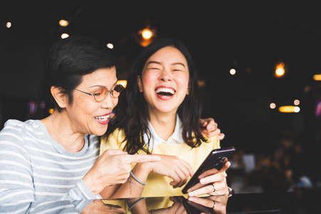 Asian mother and daughter laughing and smiling on a selfie or photo album, using smartphone together at restaurant or cafe, with copy space. Family love, holiday activity, or modern lifestyle concept Stockfoto