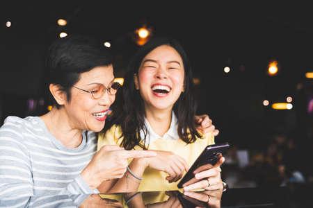 Madre e hija asiáticas riendo y sonriendo en un selfie o álbum de fotos, usando el teléfono inteligente juntos en el restaurante o cafetería, con espacio de copia. Amor familiar, actividad navideña o concepto de estilo de vida moderno Foto de archivo