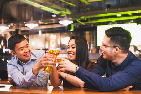 Group of happy Asian friend or office colleague coworker celebrate toast beer pint together at pub restaurant or night club. After work party, team success event or modern friendship lifestyle concept