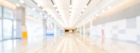 Verschwommener Bokeh-Panorama-Bannerhintergrund der Ausstellungshalle oder des Flurs des Kongresszentrums. Business-Messe-Event, moderne Innenarchitektur oder Seminar-Konzept für Handelsmessen