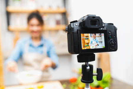 Young cute Asian blogger girl recording video tutorial session of salad cooking lesson at home kitchen. Food blogging, social media hobby broadcasting, or online learning course concept Stock Photo
