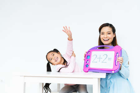 Young cute happy little girl learning simple mathematic equation, beautiful Asian mother teach using toy board. Smart kid, child family education, or children growth development with fun study concept