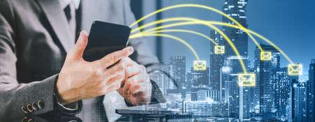 都市の背景に電子メールを送信するスマートフォンを使用して起業家ビジネスマンの二重露出バナー。ビジネスコミュニケーション、インターネット情報技術、モバイル電子メールアプリケーションの概念