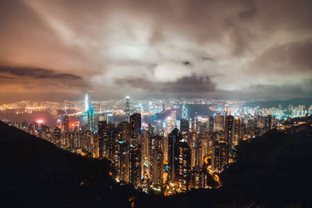 Beautiful Hong Kong island cityscape, aerial night view from Victoria Peak in cloudy storm weather. Asia tourism, business financial district, tourist attraction, or Asian travel destination concept