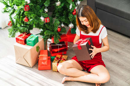 Young cute Asian girl holding red XMas present box, Christmas tree decorated with ornament at home living room. Xmas celebration event preparation, or winter holidays festival indoor party concept