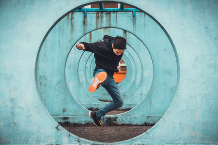 Young Asian active man in action of jumping and kicking, circle looping wall background. Extreme sport activity, parkour outdoor free running, or healthy lifestyle concept 免版税图像