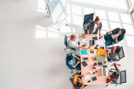 Groupe multiethnique diversifié de collègues d'affaires lors d'une réunion d'équipe, bureau moderne vue de dessus avec espace de copie. Travail d'équipe professionnel de partenariat, entreprise de démarrage ou concept de remue-méninges de projet Banque d'images