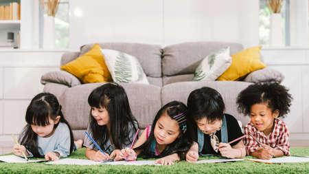 Un gruppo di cinque giovani bambini in età prescolare carini multietnici, ragazzi e ragazze felici che studiano o si riuniscono a casa o a scuola. Educazione dei bambini, stile di vita della cultura giovanile o concetto di attività di apprendimento divertente