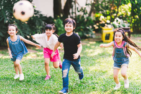 Asian and mixed race happy young kids running playing football together in garden. Multi-ethnic children group, outdoor sport exercising, leisure game activity, or childhood fun lifestyle concept