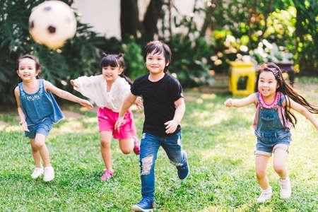 Niños felices asiáticos y de raza mixta corriendo jugando al fútbol juntos en el jardín. Grupo de niños multiétnicos, ejercicio de deportes al aire libre, actividad de juegos de ocio o concepto de estilo de vida divertido de la infancia