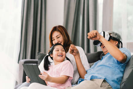 Lovely happy people playing Virtual Reality game together, young kid girl using digital tablet, grandfather wearing VR headset. Family life love relationship, or home fun leisure activity concept Reklamní fotografie